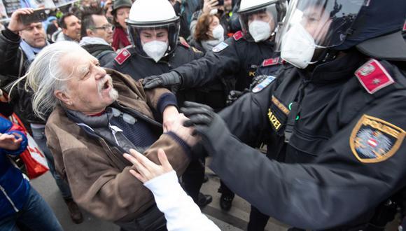 Un manifestante se enfrenta con la policía durante una manifestación contra las restricciones relacionadas con la pandemia de coronavirus (COVID-19) en Viena, Austria. (Foto: ALEX HALADA / AFP).
