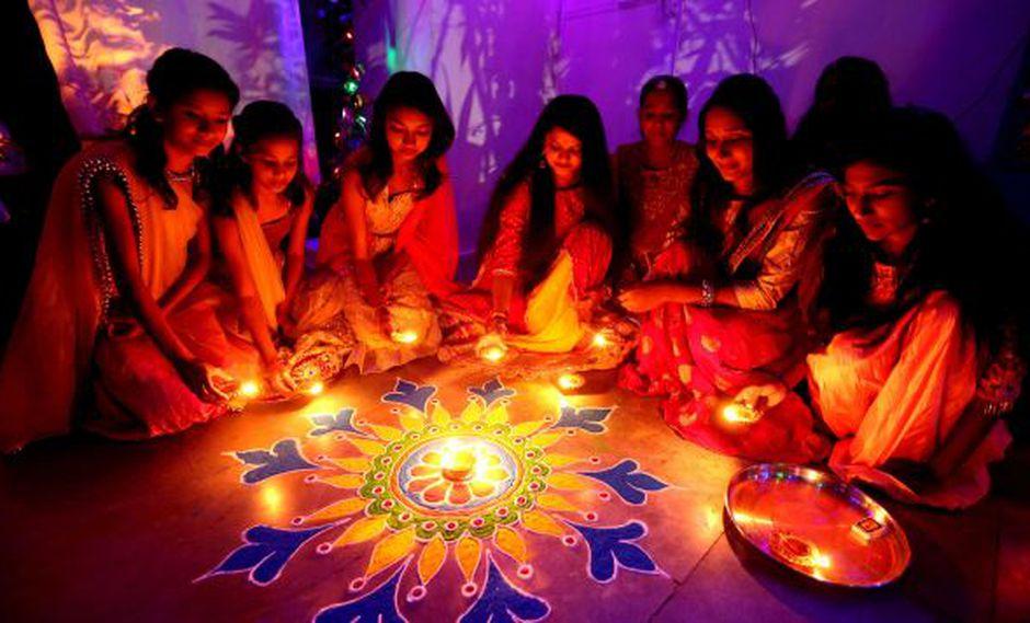 Un grupo de mujeres enciende velas sobre una flor Rangoli como decoración para el Diwali, o Festival de las Luces, en Bhopal, India. (Foto: EFE)