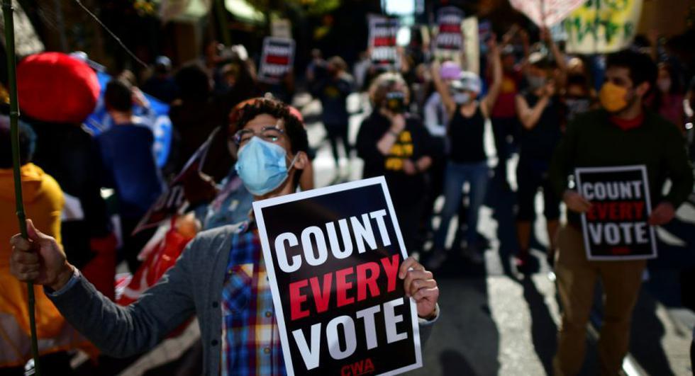 """Una persona sostiene un cartel que dice """"Cuente cada voto"""" mientras la gente se manifiesta fuera del Centro de Convenciones de Filadelfia, donde los votos todavía se cuentan dos días después de las elecciones presidenciales de EE. UU. en Filadelfia, Pensilvania. (REUTERS / Mark Makela)."""