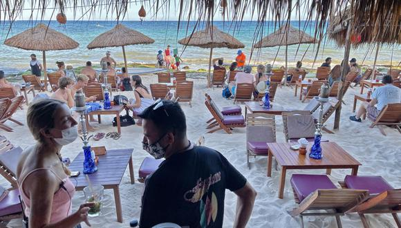 Turistas disfrutan de un restaurante de playa en Playa del Carmen, estado de Quintana Roo, México, el 3 de marzo de 2021, en medio de la pandemia de coronavirus. (Foto de Daniel SLIM / AFP).