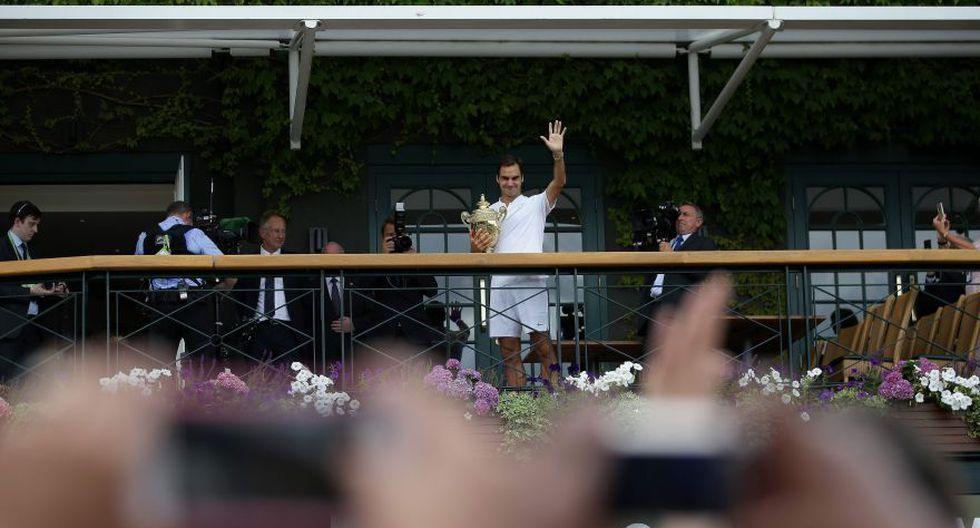 Federer presentando el trofeo de Wimbledon 2017 en el balcón ante los gritos de algarabía de los aficionados. (Foto: AFP)