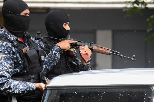 Members of the Bolivarian National Police prepare to board a vehicle after a confrontation with members of a criminal gang in the vicinity of Kota 905 in Caracas, Venezuela.  (Photo by Federico PARRA / AFP).