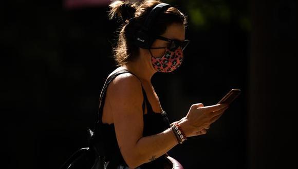 Coronavirus en España: Una mujer camina por una calle de Barcelona este jueves, en el primer día en que es obligatorio el uso de mascarillas en toda Cataluña aunque se puedan guardar las distancias. (EFE/Enric Fontcuberta).