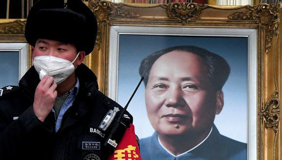 Un guardia de seguridad que usa una mascarilla se para junto a un retrato del difunto líder comunista chino Mao Zedong en un centro comercial en Beijing el 27 de enero de 2020. (Foto de Noel Celis / AFP).