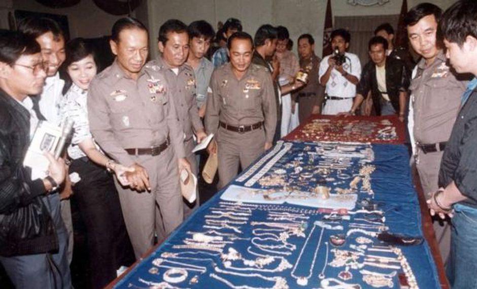 La policía tailandesa muestra algunas de las joyas que recuperaron, con Kriangkrai esposado a la derecha. (KHAOSOD).