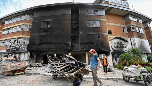 La gente saca escombros de un hotel quemado por manifestantes en la ciudad de Cali, Colombia. (Foto de LUIS ROBAYO / AFP).