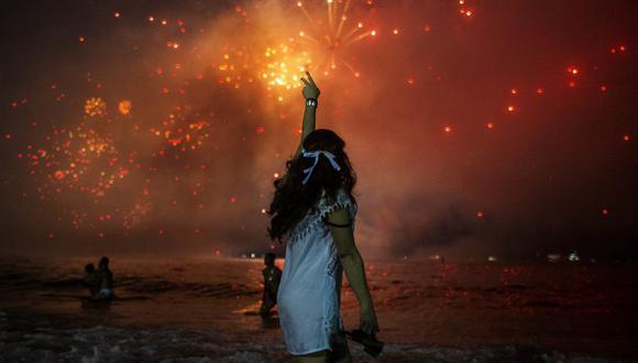 Fotografía tomada el 31 de diciembre del 2019, que muestra a una mujer celebrando el Año Nuevo y viendo los tradicionales fuegos artificiales en la playa de Copacabana, en Río de Janeiro. AFP
