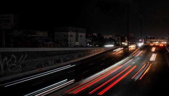 Los automóviles circulan en una carretera oscura y mientras San Juan queda a oscuras por un corte de energía debido a un ataque cibernético en Puerto Rico. (RICARDO ARDUENGO / AFP).
