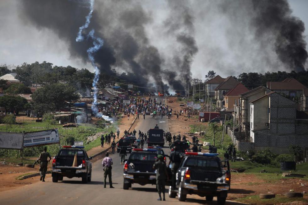 La policía nigeriana dispara gases lacrimógenos contra personas durante los enfrentamientos entre jóvenes en Apo, Abuja, Nigeria. (AFP/Kola Sulaimon).
