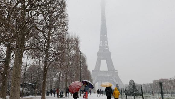 La gente camina con sombrillas en el parque Champ de Mars el 16 de enero de 2021 después de una nevada en París, mientras se ve la Torre Eiffel de fondo, en medio de la pandemia de coronavirus. (Ludovic MARIN / AFP).
