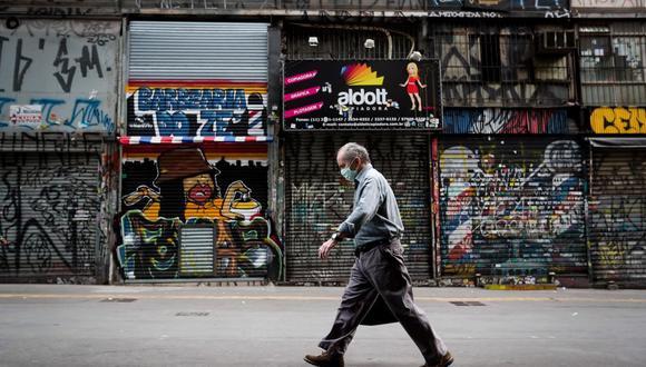 Imagen referencial. Un hombre camina frente a locales comerciales cerrados en Sao Paulo (Brasil). (EFE/ Fernando Bizerra).