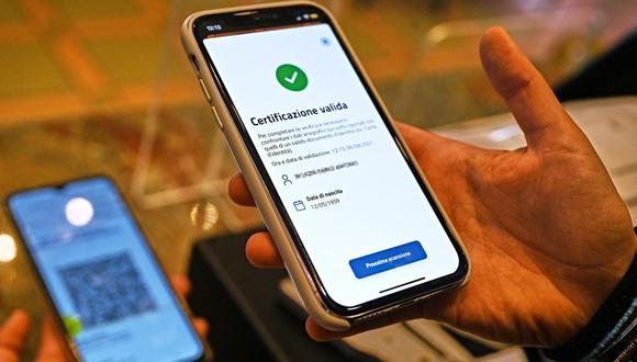 El propietario de un bar utiliza la aplicación de teléfono móvil VerifyC19 para escanear un pase verde de vacunación contra el coronavirus en el centro de Roma, Italia, el 6 de agosto de 2021. (Andreas SOLARO / AFP).
