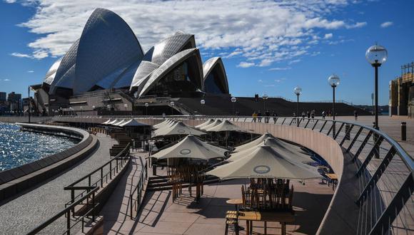 La gente camina cerca de la Ópera de Sídney el 26 de junio de 2021, luego de que las autoridades cerraran la ciudad más grande de Australia para contener un brote de la variante Delta del coronavirus. (Saeed KHAN / AFP).