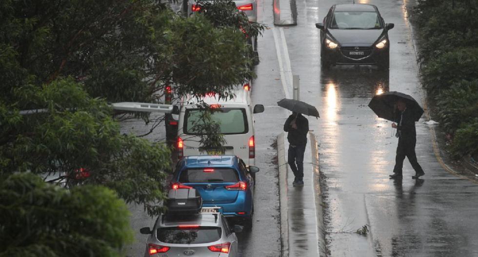 Pese al clima, los peatones desafían el fuerte viento y la lluvia en Sydney. (Reuters)
