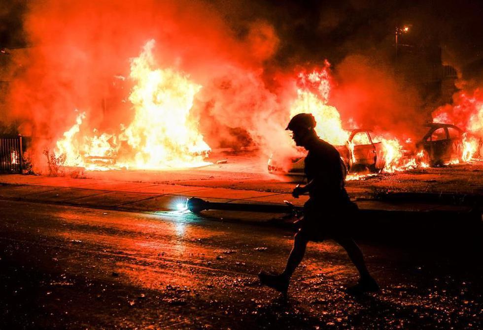 La silueta de un hombre ante varios carros incendiados durante la segunda noche de disturbios tras el tiroteo de Jacob Blake por parte de agentes de policía, en Kenosha, Wisconsin, Estados Unidos. (EFE/EPA/TANNEN MAURY).