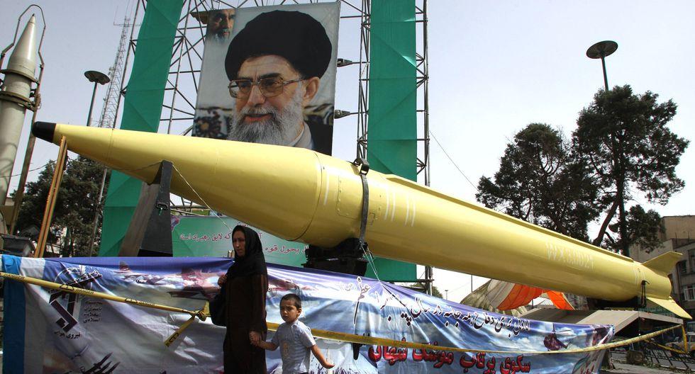 Una mujer iraní y su hijo pasan junto a los misiles Shahab-2 y Shahab-3 en exhibición frente a un gran retrato del líder supremo de Irán, el ayatola Alí Jamenei. (ATTA KENARE / AFP).