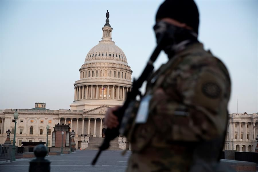 A member of the National Guard watches the Capitol. (EFE / EPA / MICHAEL REYNOLDS).
