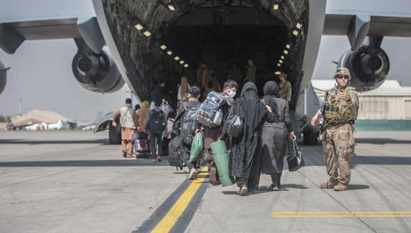 Familias afganas suben a un Boeing C-17 Globemaster III de la Fuerza Aérea de Estados Unidos durante una evacuación en el Aeropuerto Internacional Hamid Karzai, Kabul, Afganistán, el 23 de agosto de 2021. (SAMUEL RUIZ / US MARINE CORPS / AFP).