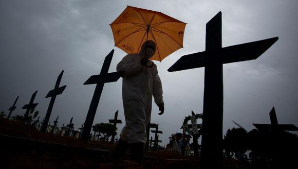 Un trabajador con traje de protección y paraguas camina frente a las tumbas de las víctimas del coronavirus COVID-19 en el cementerio Nossa Senhora Aparecida, en Manaos, Brasil, el 25 de febrero de 2021. (Foto de MICHAEL DANTAS / AFP).