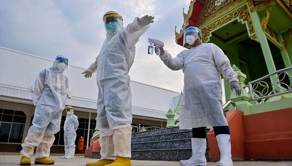 Un escuadrón de voluntarios se prepara para trasladar fallecidos de COVID-19 en Tailandia. (Foto: Lillian SUWANRUMPHA / AFP)