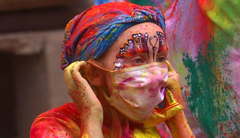 Una turista extranjera usa una máscara en medio del temor a la propagación del coronavirus en el festival de colores Holi. (AFP).