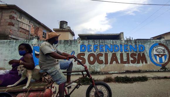 """Un hombre conduce su triciclo cerca de un graffiti donde dice """"Defendiendo el socialismo"""" en La Habana, el 12 de julio de 2021. (Foto de YAMIL LAGE / AFP)."""