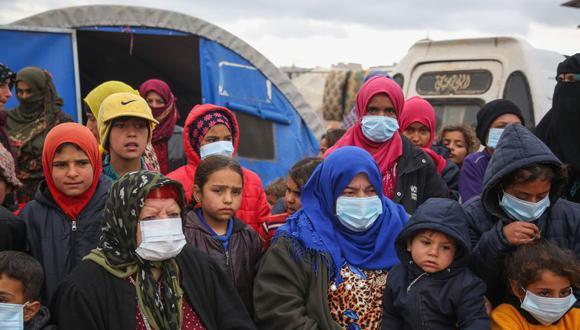 Sirios desplazados, algunos con máscaras protectoras, escuchan mientras los médicos realizan una campaña de sensibilización sobre cómo protegerse contra el coronavirus, en un campamento para desplazados en Kafr Lusin, en la provincia de Idlib. (Foto: AFP)