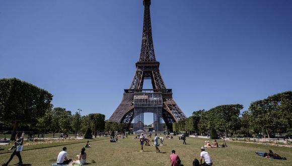 La torre Eiffel reabre tras 8 meses de clausura por la pandemia de COVID-19. En la foto, la gente toma el sol bajo un cielo azul en el parque Champs de Mars con la Torre Eiffel al fondo, en París, el 13 de junio de 2021. (Foto de archivo: Sameer Al-DOUMY / AFP)