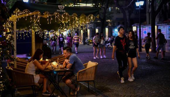 Una pareja cena en un restaurante mientras los peatones pasan caminando en Wuhan, provincia central de Hubei. China está reformulando a Wuhan como una víctima heroica del coronavirus. (Foto: Hector RETAMAL / AFP).