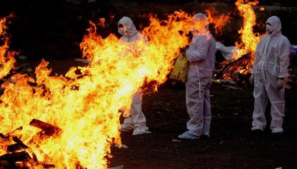 Familiares con equipo de protección personal caminan en medio de piras funerarias encendidas mientras realizan los últimos ritos para las víctimas del coronavirus covid-19 en Bhopal, India. (EFE / EPA / SANJEEV GUPTA).
