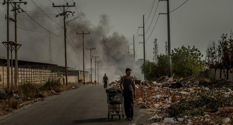 En Maracaibo, dos hombres revisaban los desperdicios en busca de objetos que todavía sirvieran o que pudieran ser reciclados. (Meridith Kohut para The New York Times).