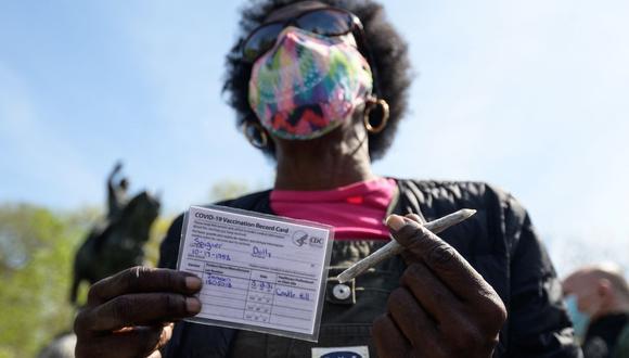Una mujer muestra una tarjeta de vacunación. Activistas de la marihuana entregan porros gratis a los neoyorquinos vacunados. (Foto: AFP)