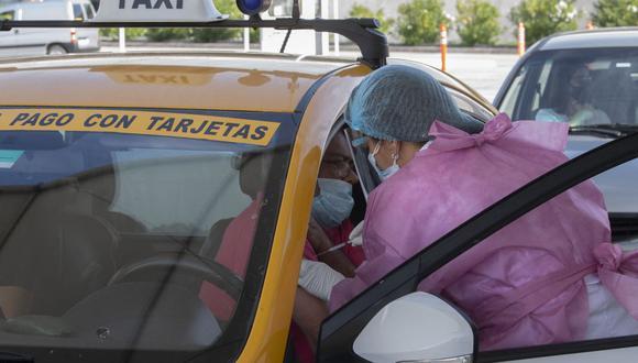 Un taxista es inoculado con la vacuna CoronaVac, desarrollada por el laboratorio chino Sinovac contra el coronavirus, en un centro de vacunación montado en el aeropuerto de Carrasco en Ciudad de la Costa, Canelones en Uruguay, el 8 de abril de 2021. (Pablo PORCIUNCULA / AFP).