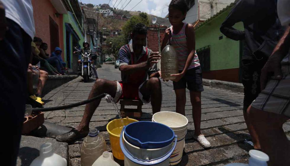 Vecinos de El Millo en los mecedores se surten de una toma de agua en la calle por las fallas en el suministro de agua potable en Caracas. (Foto: EFE)