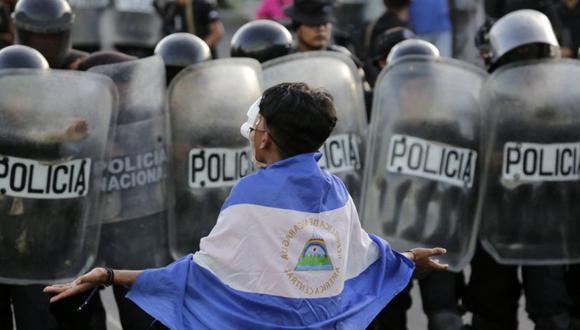 Un joven enmascarado protesta contra el gobierno del presidente nicaragüense Daniel Ortega frente a una línea de policías antidisturbios que bloquea una calle en Managua, el 13 de septiembre de 2018. (Foto: Inti OCON / AFP).