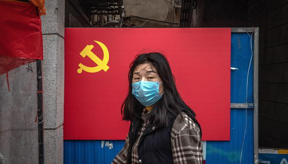 Una mujer con una máscara facial protectora camina por una zona residencial de Wuhan la ciudad china donde se inició la pandemia de coronavirus. (EFE / EPA / ROMAN PILIPEY).
