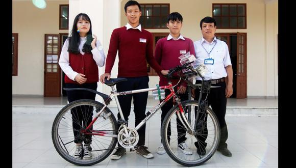 Tras seis meses de trabajo y largas deliberaciones entre ellos, los tres aprendices de científico y su profesor, Le Thanh Hai, muestran orgullosos la rudimentaria bicicleta. (Foto: EFE)