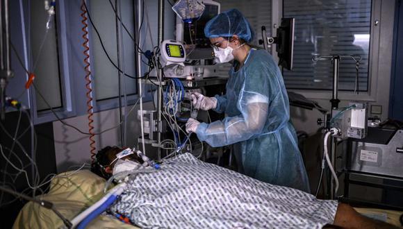 Una enfermera brinda tratamiento a un paciente con Covid-19 bajo asistencia respiratoria, en una habitación de la unidad de cuidados intensivos del hospital AP-HP Cochin en París, ya que el número de personas hospitalizadas está en el auge de la capital francesa. (Foto: Christophe ARCHAMBAULT / AFP).