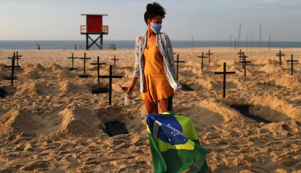 Brasileños críticos de la respuesta ambigua de su gobierno a la pandemia del coronavirus cavaron 100 tumbas y clavaron cruces negras en la arena de la playa de Copacabana en Río de Janeiro. (REUTERS/Pilar Olivares).