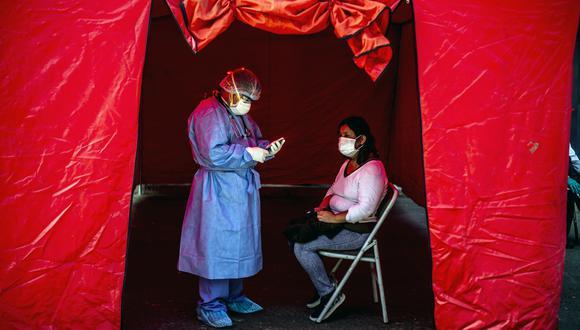 Un trabajador de salud toma un test de COVID-19 a una persona, en Lima (Foto: ERNESTO BENAVIDES / AFP)