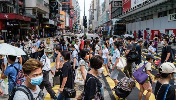 Peatones que usan mascarilla para protegerse del coronavirus caminan por una avenida principal en Hong Kong el 20 de julio de 2020. (Foto: ANTHONY WALLACE / AFP).