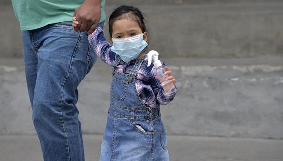 Una niña sostiene una botella de alcohol en gel durante la segunda vuelta de las elecciones presidenciales en Ecuador el 11 de abril de 2021, en medio de la pandemia de coronavirus COVID-19. (Foto de CAMILA BUENDIA / AFP).