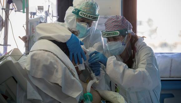 Una doctora y una enfermera de la Unidad de Cuidados Intensivos del Hospital Morales Meseguer de Murcia cambian el respirador a un paciente ingresado por COVID-19. (Foto: EFE).