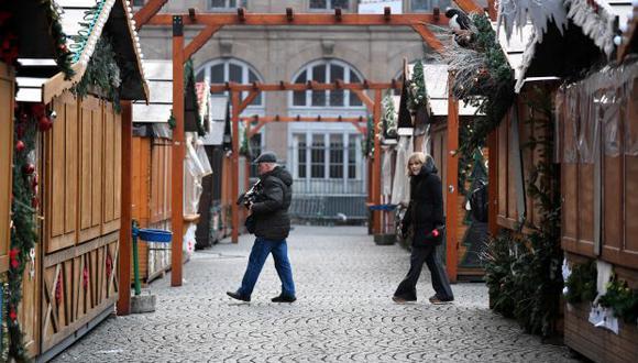 Dos reporteros caminan entre las casetas cerradas del mercadillo navideño objeto de un atentado. (Foto referencial: EFE)