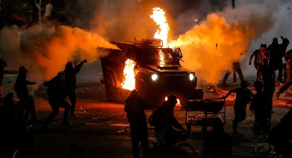 Manifestantes queman un vehículo de la policía antidisturbios durante los enfrentamientos tras una protesta contra el gobierno del presidente chileno Sebastián Piñera en Santiago. (AFP / JAVIER TORRES).