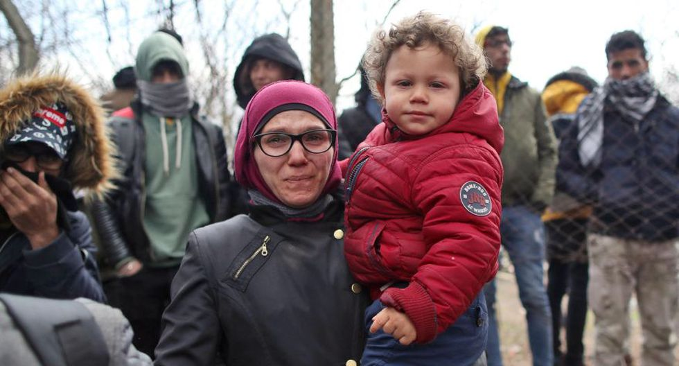 Una madre refugiada con su hijo se encuentran en el lado turco de la frontera cerrada entre Turquía y Grecia, Edirne, Turquía. (Foto: AFP).