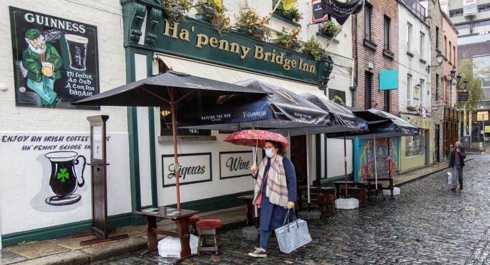 Un peatón que lleva una máscara facial o se cubre debido a la pandemia de COVID-19, pasa frente a un pub en Dublín en medio de informes de que se podrían imponer más restricciones de bloqueo para ayudar a mitigar la propagación del nuevo coronavirus. (PAUL FAITH / AFP).
