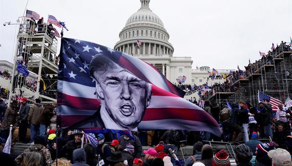 Foto del 6 de enero de 2021 donde aparecen varios simpatizantes de Donald Trump ondeando banderas con su imagen durante el asalto al Capitolio. (EFE/EPA/Will Oliver).