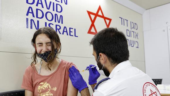 Una menor israelí recibe una dosis de la vacuna Pfizer / BioNTech contra el coronavirus Covid-19 durante una campaña del municipio de Tel Aviv-Yafo para fomentar la vacunación de adolescentes en Israel. (Foto de JACK GUEZ / AFP).
