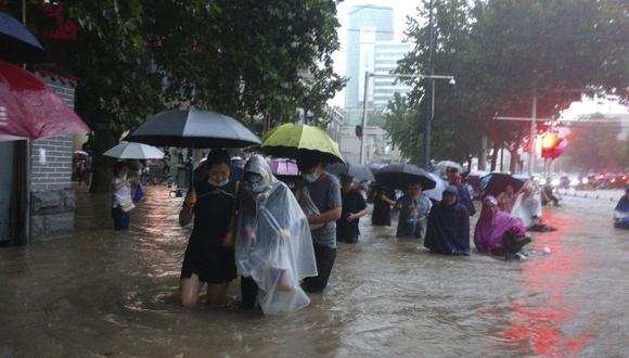 Las personas se mueven a través del agua de la inundación después de un fuerte aguacero en la ciudad de Zhengzhou, provincia de Henan, en el centro de China, el martes 20 de julio de 2021. (Chinatopix/AP).